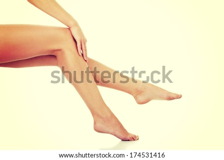 Naked long legs of sitting woman. Her hand is touching skin on smooth calf.  - stock photo