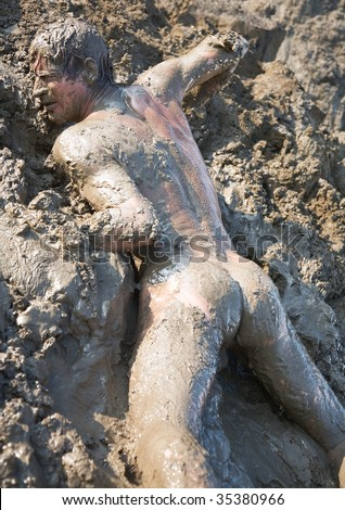 Naked man covered in mud