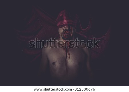 naked man on large red cloth over his eyes - stock photo