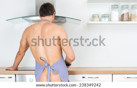 Naked man preparing food in the kitchen. View from the back. - stock photo