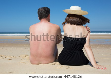 Naked man with a woman sitting on the beach. Back view