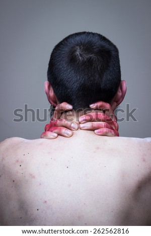 Naked man with his back turned, red painted hands on his neck - stock photo