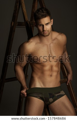 Naked man with ladder - stock photo