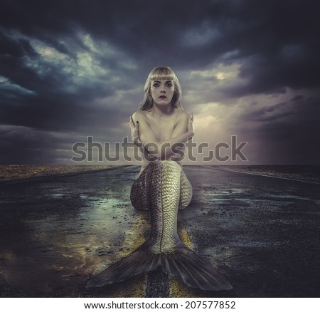 naked mermaid sitting on a deserted road - stock photo