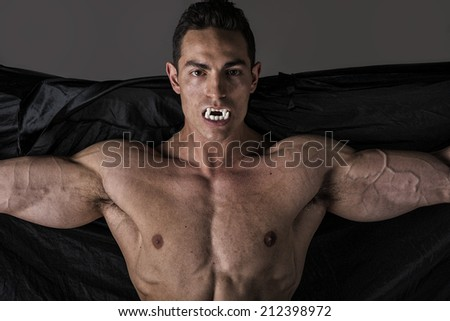 Naked muscular fit young man posing as a vampire or Dracula in a black cloak showing off his powerful body bearing his fangs with arms spread open - stock photo