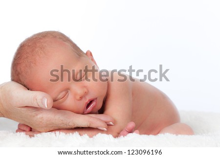 Naked newborn baby lying on caring mothers hand sleeping peacefully on white background