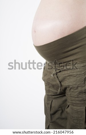 naked paunch pregnant woman with green trousers over white background - stock photo