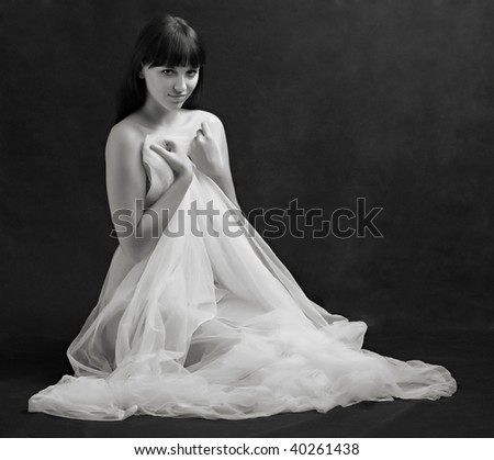Naked sexy beautiful slenderness young woman in bridal veil on black background. Monochrome studio shot. Great for calendar. - stock photo