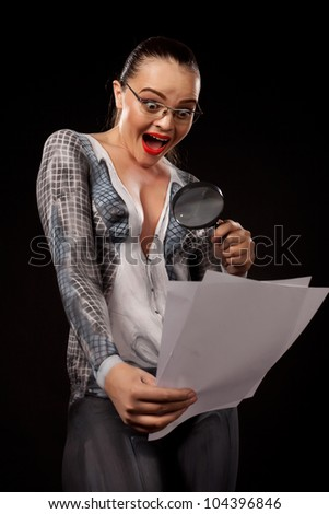Naked shocked woman covered with body paint  business suit, holding a magnyfing glass and blank documents. Concept image of sexual issues at work. High resolution studio picture on black background. - stock photo