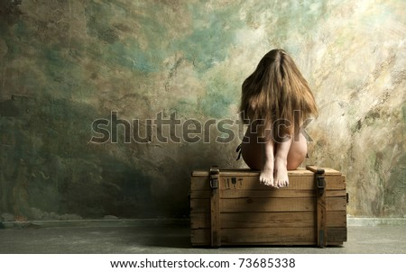 Naked  skinny woman sitting on a wooden chest - stock photo