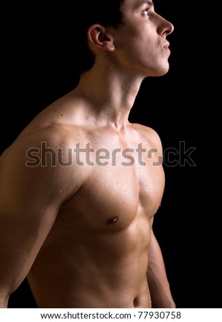 Naked torso of young muscular man on black background - stock photo