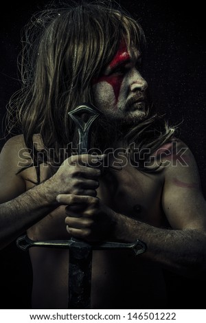 naked warrior carrying steel sword, painted face - stock photo
