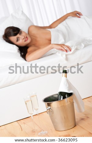 Naked woman in white bed with champagne and two glasses