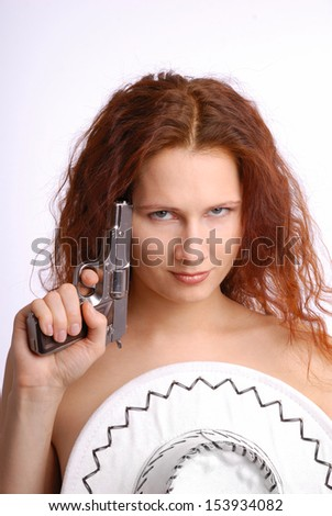 Naked woman is covering her breast with a white hat and folding a silver pistol. She is looking point-blank at the camera. - stock photo