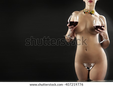 naked woman on a dark background with wine glasses and a martini glass - stock photo