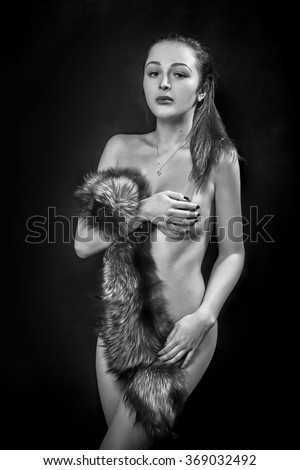 naked woman with fur on black background, monochrome - stock photo