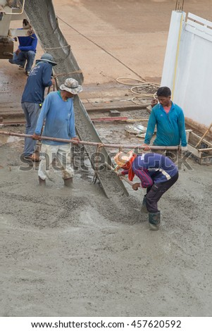 NAKHON RATCHASIMA -JULY 6 : A cement truck and worker are pouring cement to new floor at construction site on July 6, 2016 in Nakhon Ratchasima, Thailand