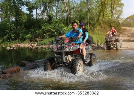 NAKHONNAYOK, THAILAND - DECEMBER 19 : Tourists riding ATV to nature adventure on dirt track on DECEMBER 19, 2015, Thailand. - stock photo