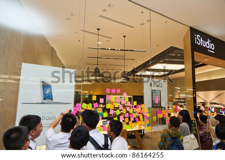 NAKHONRATCHASIMA, THAILAND - OCT 7 : Students and visitors write tributes to the late Steve Job on post-it-notes on iStudio glass wall on October 7, 2011 in Nakhonratchasima, Thailand. - stock photo