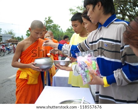 NAKHONSAWAN,THAILAND-OCTOBER 31: People put food in the monk bowls in Devorohana Festival (Buddha came back from heaven after giving 3 months sermon to his mother) on October 31, 2012 in Nakhonsawan.