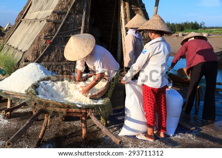 Nam Dinh, VietNam, june 20, 2015: farmers not identified, are harvested salt