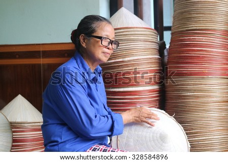 NAMDINH, VIETNAM - June 14, 2015: An elderly woman sat sewing the traditional conical hats at a handicraft villages of Namdinh. This is a woman's hat is the most popular Vietnam