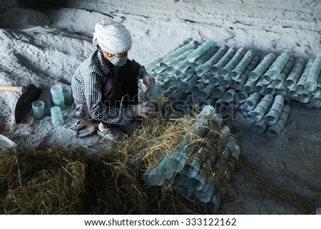 NAMDINH, VIETNAM - OCT 29: Vietnam farmer packing glass cup and give to market  in countryside at October 29, 2015 in Namdinh, vietnam. This is tradition work of farmer in village.