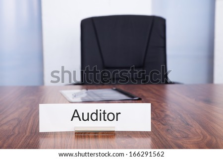 Nameplate With Auditor Title Kept On Desk In Front Of Empty Chair - stock photo