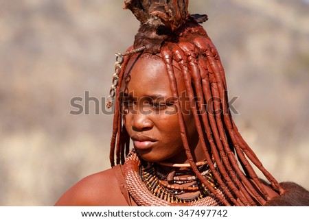 NAMIBIA, KAMANJAB, OCTOBER 10: Himba tribe woman with ornaments on the neck, in the village of Himba people near Kamanjab in northern Namibia, October 10, 2014, Namibia  - stock photo