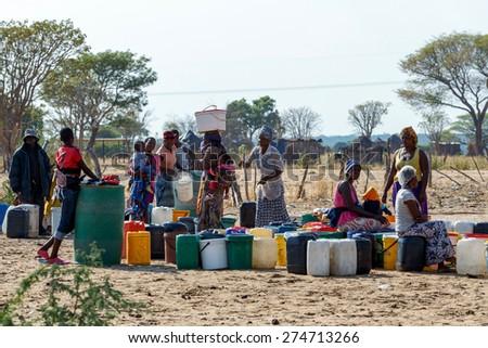 NAMIBIA, KAVANGO, OCTOBER 15: Unidentified Namibian woman with child near public tank with drinking water.Kavango region. October 15, 2014, Namibia - stock photo