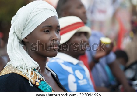 Nampula, Mozambique - November 10, 2014: Young beautiful  woman wearing traditional scarf attends a public event in Northern Mozambique - stock photo