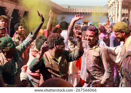 NANDGAON - FEB 28: Devotees throw colors and dance during the Holi celebration at Krishna temple on February 28, 2015 in Nandgaon, India. Holi is the most celebrated religious festival in India.