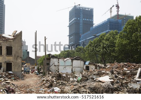 NANJING, CHINA - APRIL 29, 2016: Demolished houses with debris on the ground, for renovation building activity, new construction with cranes background