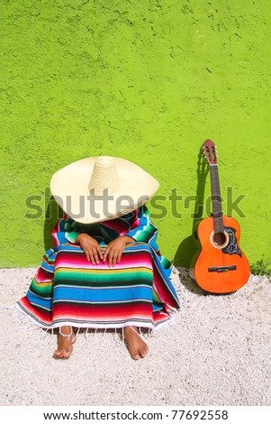 Nap lazy typical mexican sombrero man sitting on green wall - stock photo