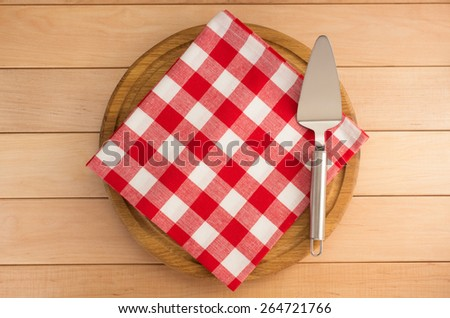 napkin at cutting board on wooden background - stock photo