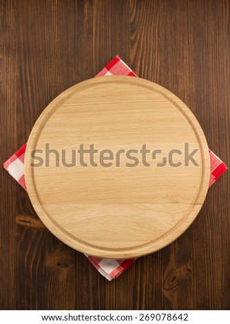 napkin cloth and cutting board on wooden background - stock photo