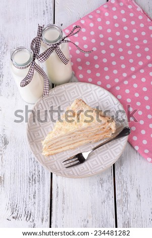 Napoleon cake with milk on table close-up - stock photo