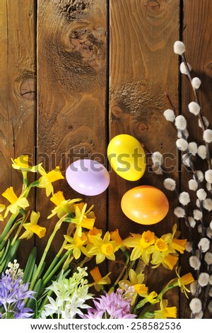 narcissus, easter eggs, easter basket and catkin on old weathered wooden board - stock photo