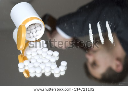 Narcotics on a mirror. Out of focus reflection of a drinking businessman. - stock photo