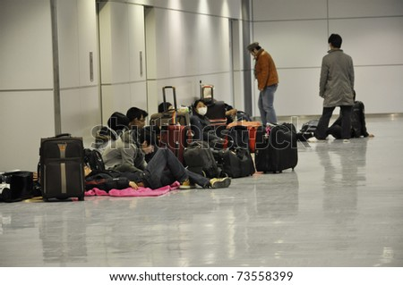 NARITA AIRPORT, JAPAN - MARCH 18 : People spend the night at Narita airport in Tokyo on March 18, 2011. Some wait for delayed or cancelled flights, others want to make sure they catch their flight. - stock photo