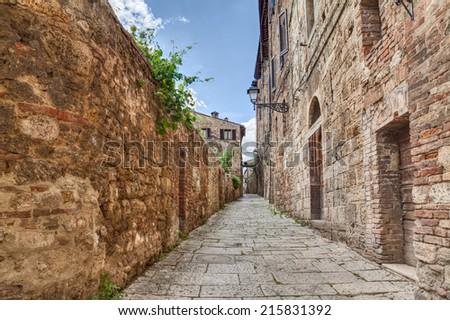 narrow alley in Colle di Val d'Elsa, Siena, Tuscany, Italy - picturesque ancient alleyway in tuscan medieval town   - stock photo