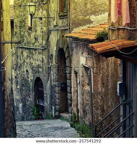 Narrow Alley with Old Buildings in Italian City of Cave, Vintage Style Toned Picture - stock photo