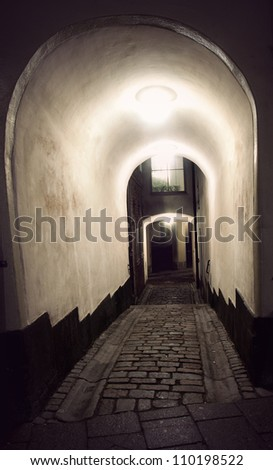 Narrow ancient vaulted street in the old town of Stockholm - stock photo
