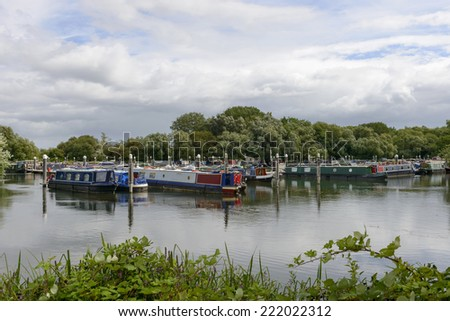 narrow boats at Thames and Kennet Marina, Reading view of river harbor for narrow boats on river Thames, shot under cloudy yet bright sky  - stock photo