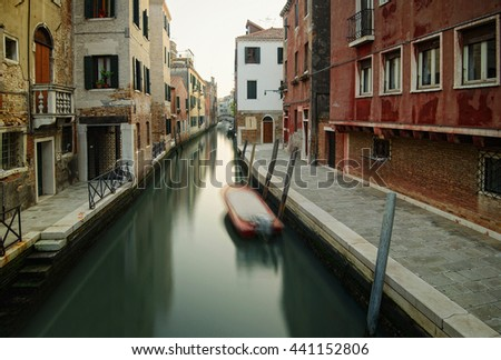 Narrow canal in Venice. Boats and reflection of colorful houses in the water. Long time exposure.  - stock photo