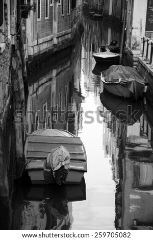 Narrow canal in Venice. Boats and reflection of houses in the water. Selective focus on the reflection. Aged photo. Black and white. - stock photo