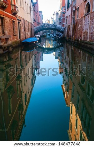 Narrow canal in Venice. Reflection of buildings in water, and the bridge in the background. Italy - stock photo