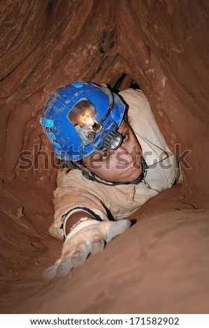 Narrow cave passage with a cave explorer - stock photo