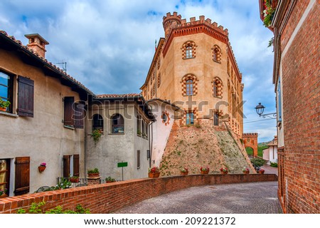 Narrow cobbled street and medieval castle among old houses in town of Barolo in Piedmont, Northern Italy. - stock photo