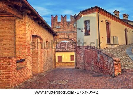 Narrow cobbled street in old historic center of Monticello D'Alba - small town in Piedmont, Northern Italy. - stock photo